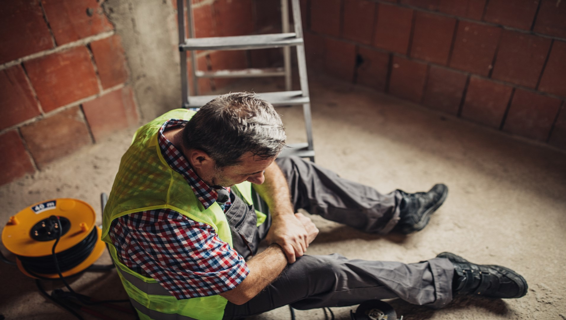 Male tradesman with osteoarthritis in his knee at work