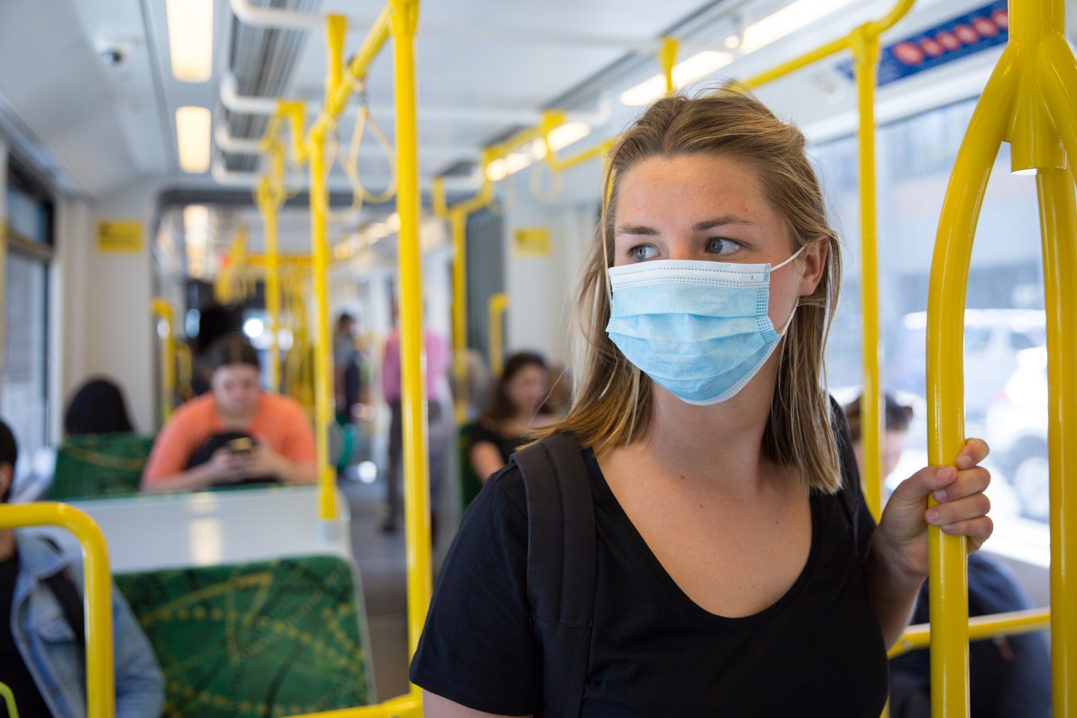 Woman in COVID-19 face mask on public transport