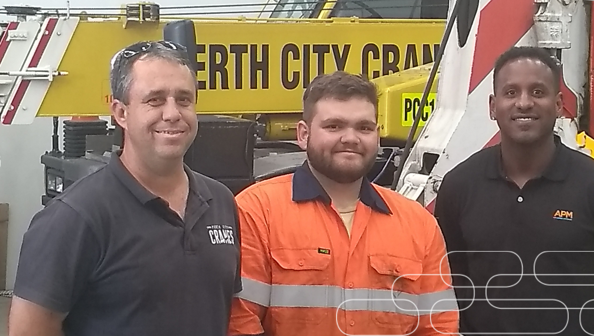 Jake stands, dressed in his hi-vis work uniform between his Perth City Cranes boss and his APM consultant