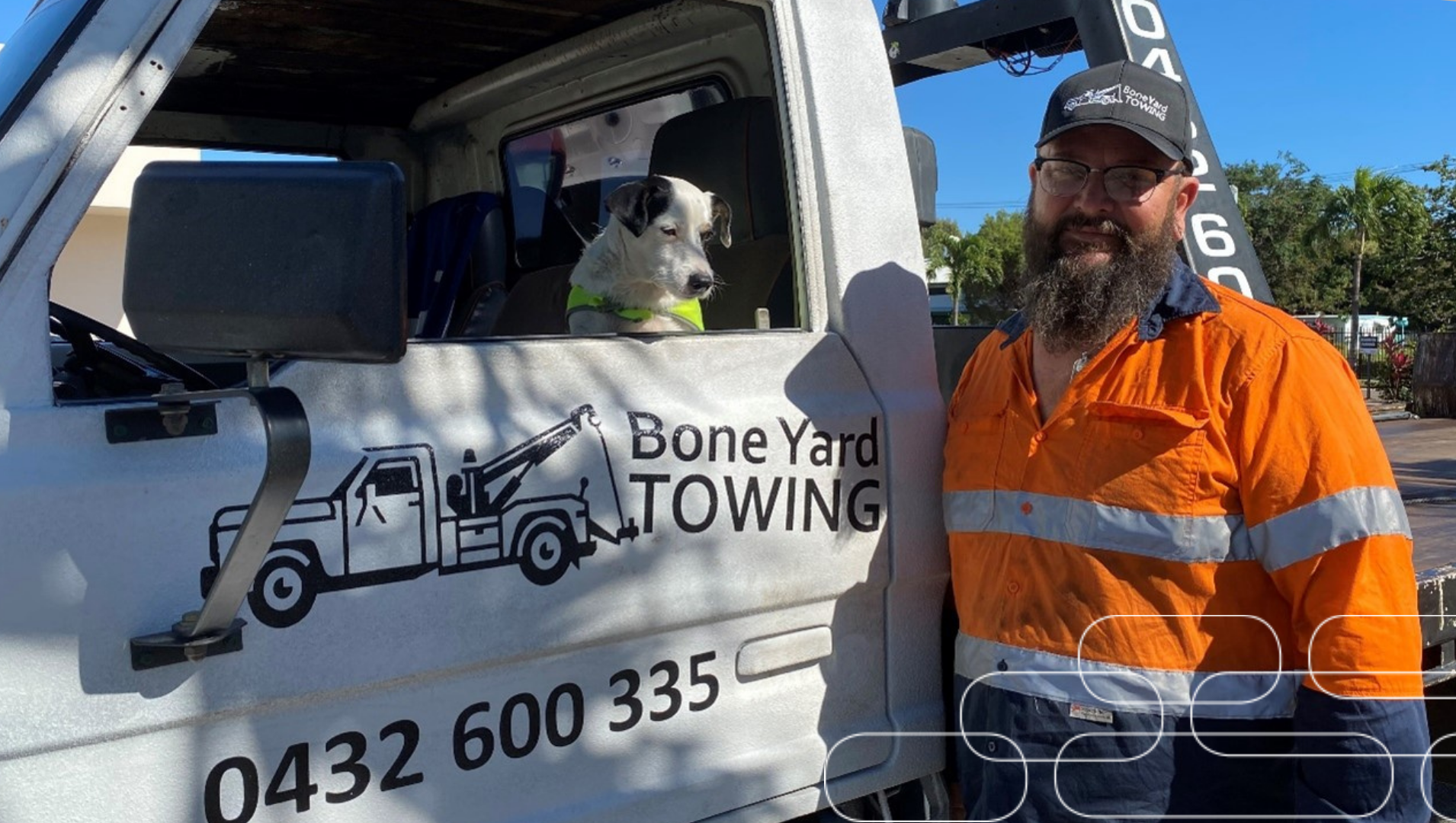 Scott standing in his hi-vis work uniform standing next to the side door of his tow truck, with his company label showing, and his support dog buddy sitting inside the cab of the truck